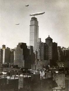 29. Oktober 1930    Der Zeppelin ZR-3 Los Angeles fliegt an dem sich noch im Bau befindlichen Empire State Building vorbei. Ursprünglich sollte der 381 Meter hohe Betonturm auch als Landeplatz für Luftschiffe dienen. Passagiere sollten über Laufplanken zu- und aussteigen können. Die Idee wurde jedoch schnell verworfen. Die Aufwinde waren zu stark, ein Andocken an das Gebäude kaum möglich und für die Passagiere viel zu gefährlich.