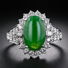 A vibrant, forest green cabochon oval jade - accompanied by an American Gemological Laboratory certificate stating: Natural Color - is elegantly presented inside a sparkling diamond halo, punctuated on each side with a baguette diamond, and a sparkling pave' diamond ring shank. Superbly crafted in platinum, circa 1960s-70s, with bright-white high-quality diamonds.