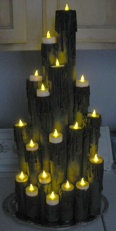 A spooky candle display without any fire danger: Wrapping paper tubes, paper towel tubes and TP tubes, hot glue for the drips, all painted with a flat black spray paint, and battery operated tea lights.