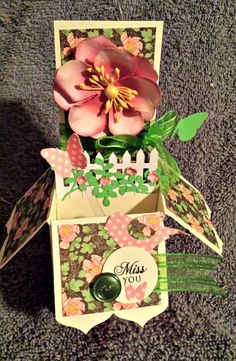 Garden box card - Scrapbook.com - Use a large flower and die cut fence on a pop up box card to create a little garden inside the box.