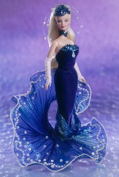 "Water Rhapsody Barbie The Essence Of Nature Collection Limited Edition Release Date: 1/1/1998 First in the Collection. Barbie® doll is emerging from the water in her blue velvety dress enhanced by a striking ""wave"" train of pleated iridescence with faux pearl and sequin. Her intricate scalloped sequin and bead headpiece features clear-beaded tendrils replicating the delicate sea spray. Her ensemble is complete with white mesh fingerless opera-length gloves and a wide blue bead and sequin…"