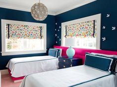 Contemporary navy blue and hot pink girls' bedroom is lit by a Capiz Flower Chandelier hung between beds dressed in blue and white bedding topped with navy blue velvet pillows placed in front of a long shared hot pink headboard.