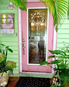 Cottage with Pink Front Door and Mermaid Art: http://www.completely-coastal.com/2015/05/tropical-florida-garden-with-mermaid-art-shells-buoys.html