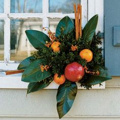 Magnolia leaves fan out, dotted with oranges and cinnamon-stick accents in this window-mounted decoration.