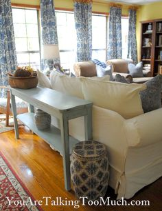 The simple use of a long rug and narrow table behind the couch establishes separation between the living space and the entryway, yet takes advantage of the large, open floor plan.