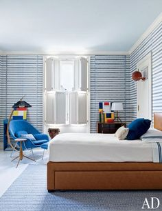 A blue-striped boy's room by Stephen Sills features a Saarinen womb chair and ottoman from Design Within Reach.