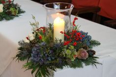 Hurricane lamps surrounded by Christmas wreaths of Hydrangeas, Roses, Berries, Fir Cones and seasonal foliages and herbs, the heat from the candles helped to circulate the fragrances