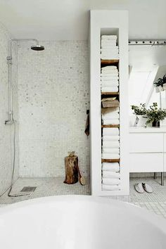 Linear shelf wall for end of shower houses towels facing room and shower niche deeper end