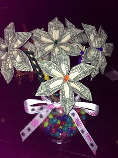 Money flowers I made for my sisters bday. I bought all materials at dollar tree (vase, floral foam, pipe cleaners, ribbon, skittles) I used a video on YouTube to make the money flowers. http://m.youtube.com/user/lisasheaorigami#/user/lisasheaorigami/about her videos are super easy to follow! Money flowers, money tree, birthday gift, money gift, DIY
