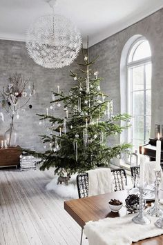 A bright, open dining room with a sparsely decorated Christmas tree perfectly shows  minimalistic holiday decor. A beautiful winter tablescape adds the finishing touch.