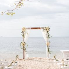 Costa Rica destination wedding beach ceremony with beautiful pastel flowers and romantic lace draping on arch. Sand ceremony inspiration.