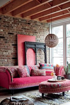 A sitting room with a bright pink sofa and lots of patterned throw pillows against a brick accent wall. It all has a bohemian flair to it, but is it so? Image by DFS Furniture.