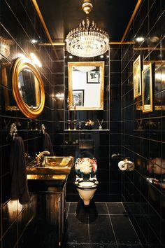 Thomas halusi yökerhomaista tunnelmaa wc:n sisustukseen. Mustat seinälaatat ovat Pukkilan mallistosta ja krokotiilinnahkakuvioinen lattialaatta on ostettu Bauhausista. Pyyhepidikkeinä toimivat kullanväriset ovenkolkuttimet, ja tyyliin sopiva lavuaari löytyi Bauhausista. Tilan kruunaa tori.fi:stä ostettu kristallikruunu. Allaskaapin Thomas on tehnyt itse.