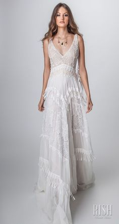 """Rish Bridal 2018 """"Sun Dance"""" Collection – Romantic Timeless Sparkly Bohemian Wedding Dress. Renee A line silhouette bridal gown. Bodice is made of bohemian elegant bohemian gentle lace embellished beaded with crystal, pearls V shaped belt, V neckline and feather tassels on the shoulder. Skirt is made of soft chiffon, panels of lace and small tassels. Light comfortable flattering sparkly bridal gown. #RishBridal #SunDance #ReneeByRish #BohoChic #BohoGown #WeddingDress #Romantic #Bride #Glam"""