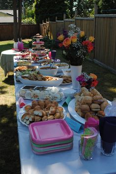 Outdoor bridal shower decor - food table with fresh flowers and colorful dishes