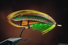 Green Highlander (Kelson - The Salmon Fly 1895).  Tag: Silver twist and canary silk.Tail: A topping and Teal.Butt: Black herl.Body: Two turns of yellow silk and green Seal's fur.Ribs: Silver tinsel.Hackle: Green from yellow silk.Throat: A yellow hackle.Wings: Two tippets (back to back) veiled with light and dark Bustard, Golden Pheasant tail, dark mottled Turkey, Swan dyed green, Mallard and a topping.Horns: Blue Macaw.