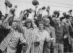 A View Into History: Photos From Dachau Concentration Camp: Survivors Welcoming Liberators. Survivors cheer the arrival of American liberators. The youth standing to the left is Juda Kukieda, the son of Mordcha Mendel and Ruchla Sta. (April 29, 1945). Picture from the National Archives, courtesy of USHMM Photo Archives.
