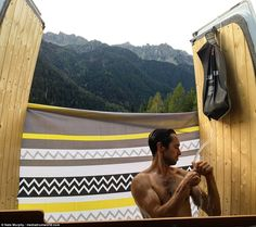 Nate Murphy showering in the converted van. He said he is planning on travelling in the va...