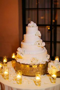 featured photographer: Priscila Valentina; stunning all white wedding cake table with candle decors