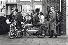 Nederland. Bromfietsen. Jongeren staan op de hoek van de straat met elkaar te praten. Sommige hebben hun bromfietsen bij zich, o.a. een Kreidler. Plaats onbekend. ca. 1980.