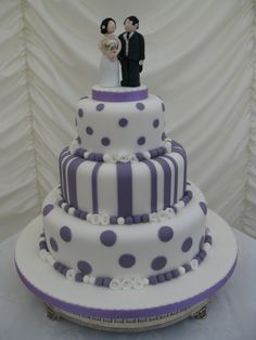 Lovely 3 tier purple and white wedding cake in stripes and spots design. Hand made bride and groom topper.