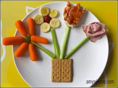 The basket of flowers is made of a graham cracker basket, celery stems, and four flowers.  Flower 1:  carrots and a grape.  Flower 2: bananas and the bottom of a strawberry.  Flower 3:  a piece of toast with jam cut into the shape of a tulip.  Flower 4: rosette made of ham.