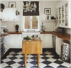 Darling small kitchen full of charm. Chandelier - Black and white checkerboard floor - warm wood counters. Wonderful balance and lots of interest.