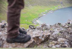 Person steht auf einem Felsen in den Bergen in der Nähe eines Dorfes am Meer, Färöer Inseln