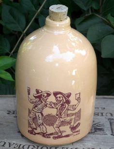 The Drinking Buddies moonshine jug is handmade from porcelain and decorated with an image borrowed from Mexican artist José Guadalupe Posada. Its