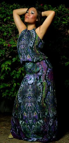 Descend into the snake pit in this reptilian backless halter dress.  A blend of silk and cotton in a python print wraps around you in rich hues of African violet, fierce fuchsia, pine green, deep emerald, hissing heliotrope, poison pear, and brilliant magenta.  With only a single seam down the back, the mirror image pattern of snakeskin is uninterrupted. The long columnar dress fits loose below the chest.  Slithering around your waist is a chain belt with charm that allows the floor length…