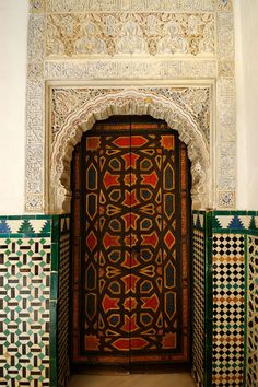 Carved doorway, Spain. Love the #tile - Handmade tiles can be colour coordinated and customized re. shape, texture, pattern, etc. by ceramic design studios
