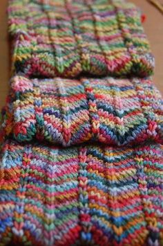 Chevron Scarf.Cast on 33 stitches. Yarn - any size needed for your gauge) dd = (double decrease is slip 2 knitwise, knit 1 - pass slipped stitches over) Row 1 - Knit 4, yo, k1, yo, k4, dd (slip 2 stitches knitwise, knit 1, pass slip stitches over), knit 4, yo, k1, yo, knit 4, dd, knit 4, yo, k1, yo, knit 4.Row 2 - P 1st 2 tog - P to last 2 sts - P2tog. Yarn - 6 different balls of Koigu - two different yarns at a time - knitting a knit and purl row with one yarn - then switching to the other.