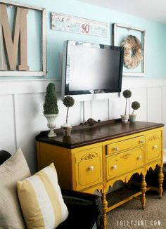 How to decorate around a tv, place frames around tv and a small sign above it to balance it out.