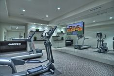 A carpeted home gym with a mirrored wall and a a widescreen LED.