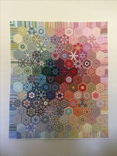 """This hexagon quilt was made mostly from men's shirts collected at The Goodwill.  I call it """" The Shirt off His Back"""" because of my friend who took his shirt off and gave it to me when I admired the plaid and wished it could be a part of my quilt. The brightest red hexagon in the center came from that shirt."""