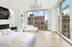 Master bedroom with wrap around window view and large chandelier