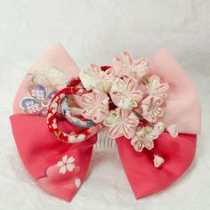 正絹の布を使用したつまみ細工のリボンかんざしです。リボンも正絹生地で制作しています。明るいピンクのリボンに柔らかな色合いの桜とアクセントに赤のちりめん紐をあし...|ハンドメイド、手作り、手仕事品の通販・販売・購入ならCreema。