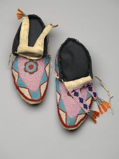 Blackfoot (Native American). Pair of Men's Moccasins, late 19th-early 20th century. Leather, beads, orange horse hair, tin, Each: 10 1/4 x 4 3/4 in. (26 x 12.1 cm). Brooklyn Museum, Charles Stewart Smith Memorial Fund, 46.96.9a-b. Creative Commons-BY (Photo: Brooklyn Museum, 46.96.9a-b_view1_PS2.jpg)