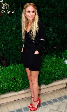 Mary-Kate Olsen in a black sweater dress and red strappy sandals.