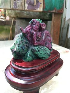 Ruby Zoisite Carved Mermaid Statue (with the stand)  Anyolite is the name used to describe the naturally occurring combination of Green Zoisite…