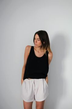 Minimal + Classic: black tank and pleated loose white shorts.
