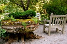 A tree trunk and a millstone come together as an ingenious planter in Les Jardins de Métis, Quebec
