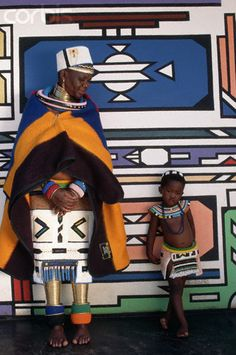 Ndebele mother and daughter standing next to their traditionally painted house by Lindsay Hebberd/Corbis