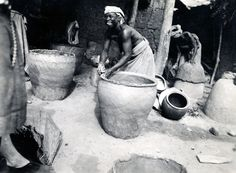 Nigeria, Yoruba [?] adult female making a large pot. Shaping rim of pot with hands. Unfinished pots at left and right. Second female forming base of pot over earth [?] dome at right, carrying young child on back. Females wearing head-cloths, cloths around lower bodies. Section-view of building in background. Leg of European [?] adult female entering picture at left. Medium: Gelatin silver print. Format: Photograph mounted on card.