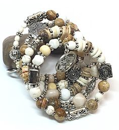 This Ohm bracelet creates a beautiful, subtle palette. It is infused with varying shades of earth tone beads. This memory wire bracelet is made with white Jade beads, white and cream glass beads, cream firepolished beads, coconut shell beads, white wood beads, picture Jasper beads and silver-toned yoga charms. This rustic bohemian bracelet is set neatly within silver-toned spacer beads. Average bead size 8mm.  This rustic boho bracelet will transition easily from day to evening wear and…