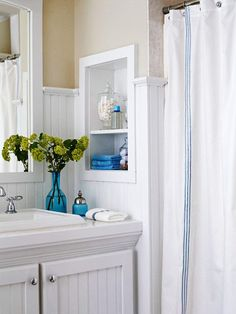 I was worried about taking my bead board up so high, but it really works here!! A new white shower curtain continues the pristine theme. Blue accents add touches of fresh color.