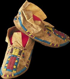 """Arapaho Moccasins, ca. 1880 - Vamp beaded with large red rectangle flanked by stacked rectangles; outer edge lane in navy, yellow, red and blue. Rawhide soles. 9"""" long. Peter Schramm Collection. Source: http://www.hmgrimmer.com/Detailed/584.html"""