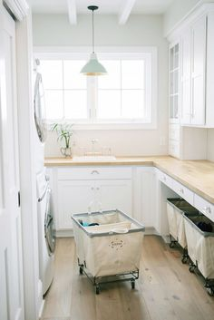 Wooden countertops, white cabinets, rolling canvas baskets, white walls, hanging blue lamp