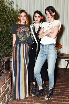 Camille Rowe in Les Bonbons earrings; Langley Fox in a Blazé Milano coat, Levi's shorts, and a Billy T-shirt; and Emily Hope