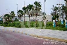 Yas Marina Cicuit West gate red brick paved parking pavement, with kerb stones and contrasting green carpet grass and palm trees